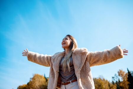 Happy smiling young girl with outstretched arms enjoying freedom.
