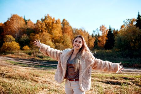 Cheerful girl with raised hands on the field in warm autumn season.