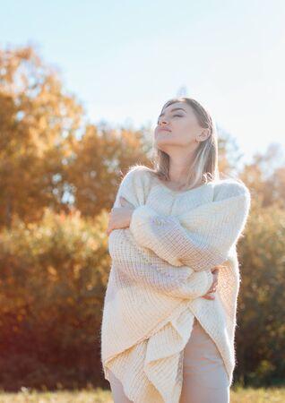 Smiling young girl hugging herself and enjoying nature. Фото со стока