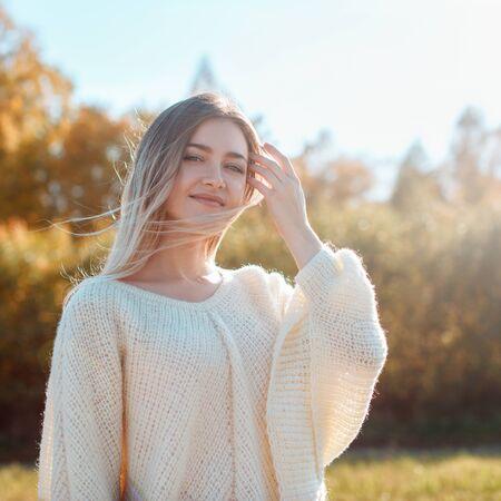 Pretty girl posing on camera and enjoying sunny autumn day.