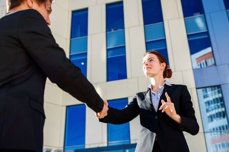Business woman and man shaking hands outdoors. Business cooperation concept Фото со стока