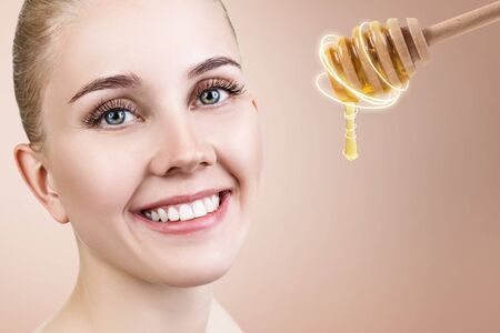 Young woman looks on spoon with honey and prepare for facial mask.