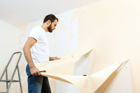 Man in with a scraper in the process of removing old wallpaper. Фото со стока