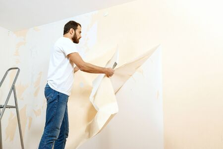 Man in with a scraper in the process of removing old wallpaper. Stockfoto