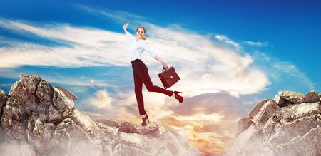 Business woman stands unstable on mountain cliff.
