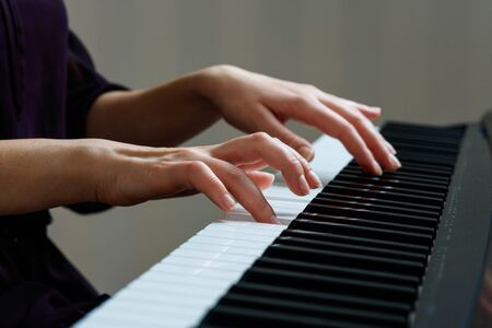 Young woman playing piano. Close up hands on the synthesizer keyboard Stockfoto