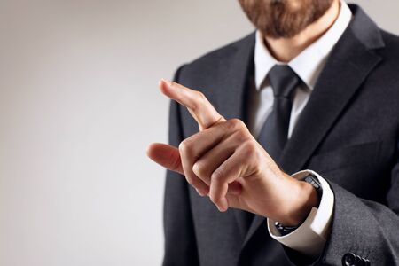 Businessman with pointing to something or touching by forefinger.