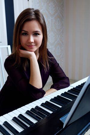 Young woman sitting and playing on the electronic piano Stockfoto