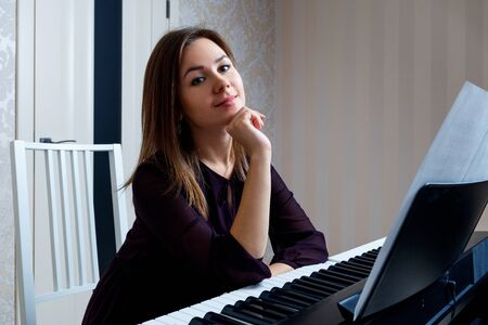 Young woman sitting and playing on the electronic piano Stock Photo