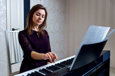 Young woman playing on the electronic piano at home.