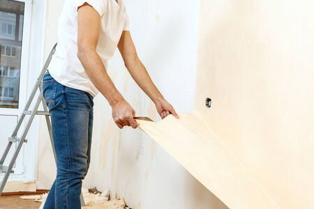 Man in with a scraper in the process of removing old wallpaper. Stock Photo