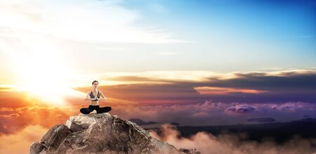 Young woman practice yoga on mountain peak cliff. Banque d'images