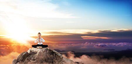 Cute little girl practice yoga on mountain peak cliff.
