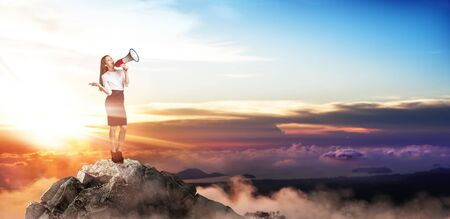 Young buiness woman with loudspeaker stands on the top of the mountain. Over beautiful sunset background.