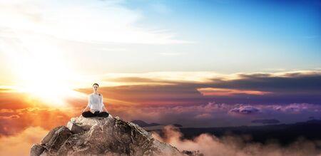 Jeune femme pratique le yoga sur la falaise du sommet de la montagne.