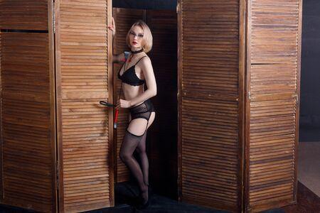 Une femme dominante blonde sexy tient un fouet sur un panneau pliant en bois