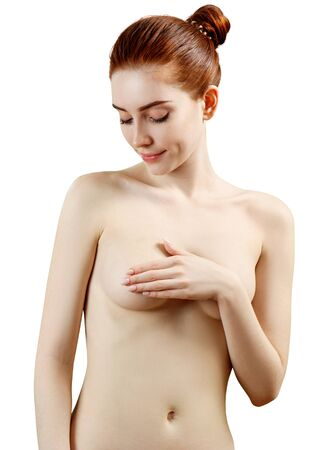 Beautiful naked redhead woman covering her breast against white background.