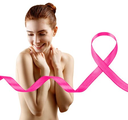 Smiling woman cover breast by hands near big pink ribbon. Banco de Imagens