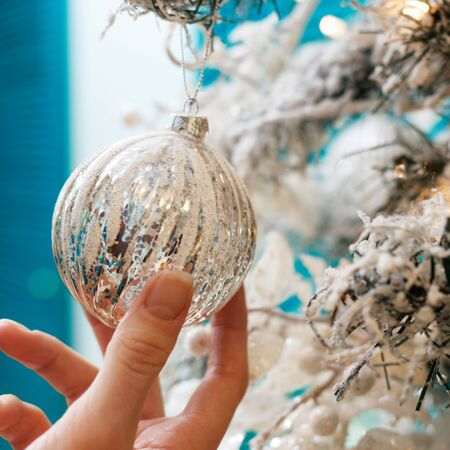 Hands decorating christmas tree with a silver balls.