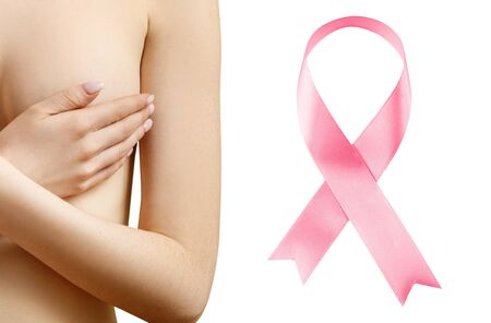 Young woman covers her breast near big pink ribbon.