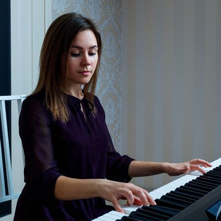 Young woman sitting and playing on the electronic piano 스톡 콘텐츠