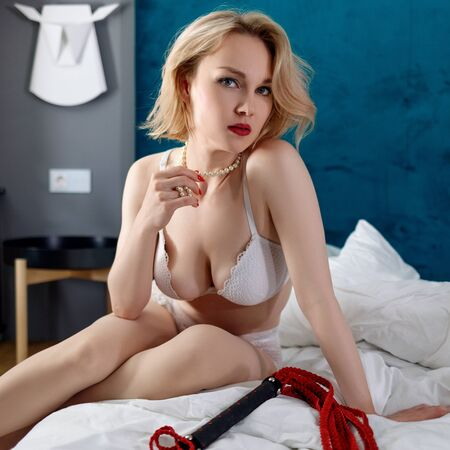 Sexy blond dominant woman in white lingerie with red whip.