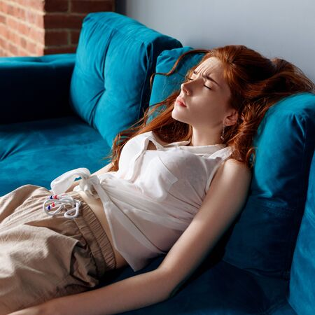 Young redhead woman reclining on the couch and feels tired.
