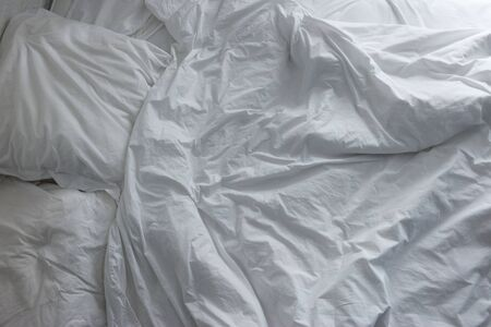 Untidy crumpled bed with white bedclothes.