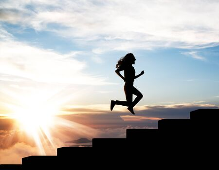 Black silhouette of woman running up on the staircase in sunset.