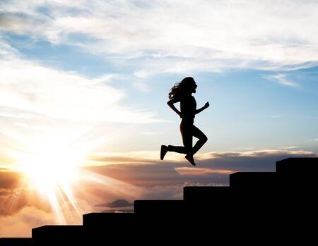 Schwarze Silhouette der Frau, die im Sonnenuntergang auf der Treppe hochläuft.