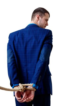 Back view on tied hands by the rope of businessman in blue suit.