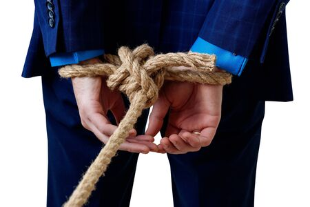 Close-up view on tied hands by the rope of businessman in blue suit.