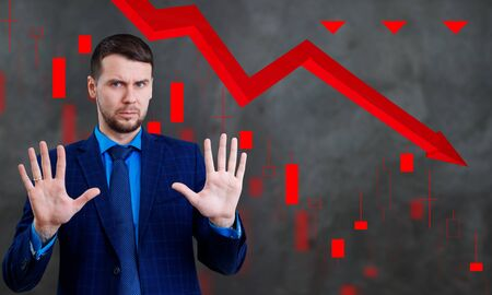 Businessman with palms shows refusal gesture over down red arrow.