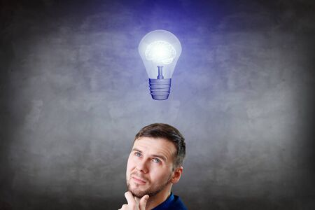 Businessman thinking and pointing finger on light bulb over head.