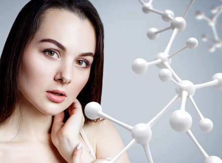 Beautiful woman near big white molecule chain.