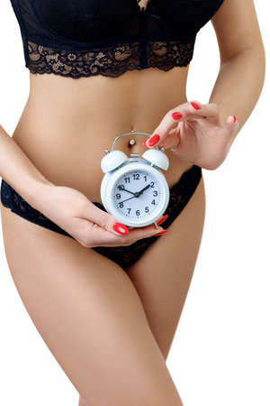Woman in black panties holding alarm clock in hands.