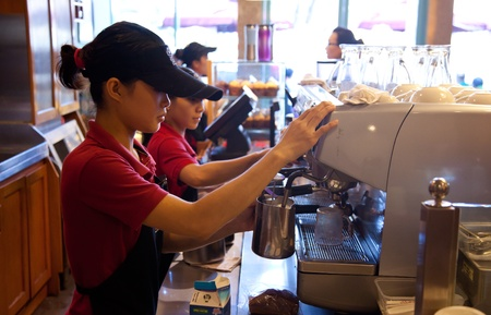 serv: Staff at a cafe in central Ho Chi Minh City making cappuccino.