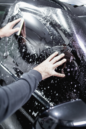 Car tinting - Worker applying tinting foil on car window. Stock fotó - 104541690