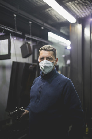Worker with protective mask in factory for production heavy pellet stoves and boilers. Archivio Fotografico