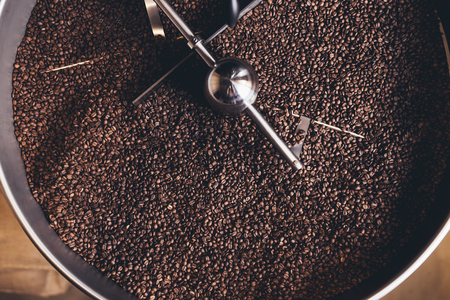 Freshly roasted aromatic coffee beans in a modern coffee roasting machine.