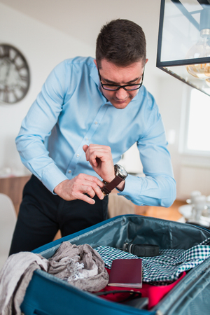 Man preparing for business travelling. Open traveler's bag with passport, clothing and accessories. Travel and vacations concept. Imagens