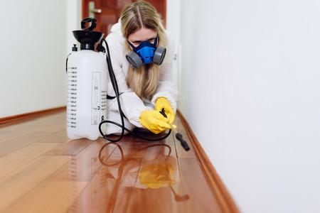 Exterminator in work wear spraying pesticide with sprayer. Zdjęcie Seryjne - 105599359
