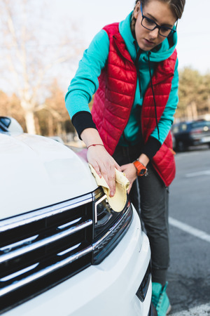 A woman cleaning car with microfiber cloth, car detailing (or valeting) concept. Selective focus. Stock Photo