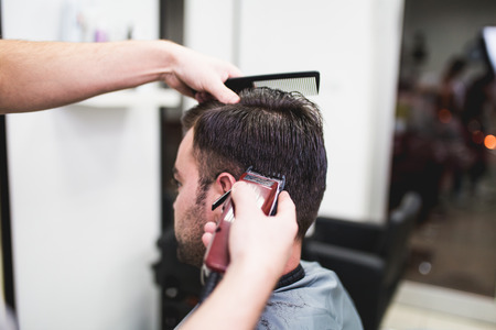 Professional barber doing a haircut to a male client. Imagens