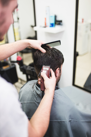 Professional barber doing a haircut to a male client. Фото со стока