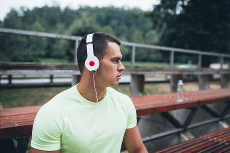 Good looking young man sitting outdoor and listening to music.