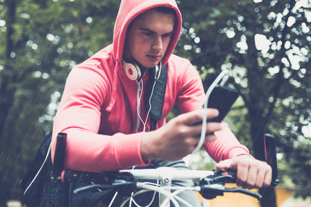 Close up of man on bike in a park, while looking at mobile phone. Rainy day.