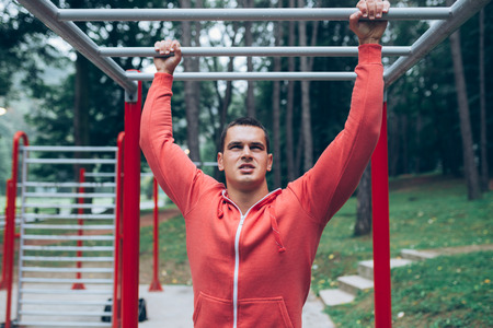 Young handsome man exercising in a park .