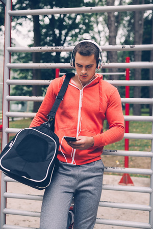 Young handsome man listening to music after a hard training outdoor. Imagens
