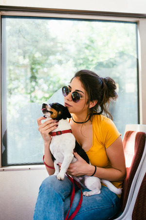 Beautiful young woman sitting in city bus with her jack russell terrier.